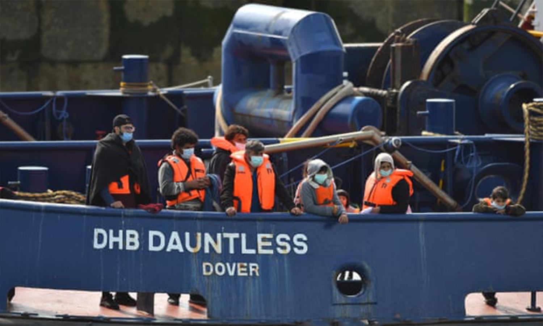 يتم إحضار المهاجرين من قبل قوة الحدود البريطانية بعد عبور القناة بشكل غير قانوني على زورق. وكالة الصحافة الفرنسية