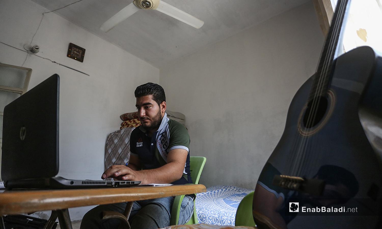 الشاب مازن الشيخ يدرس على طاولة في منزله وعلى يساره جيتار -08 أيلول 2020 (عنب بلدي/ يوسف غريبي)