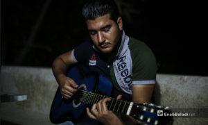 مازن الشيخ يعزف على الجيتار في منزله ببلدة عقربات شمال مدينة إدلب -08 أيلول 2020 (عنب بلدي/ يوسف غريبي)