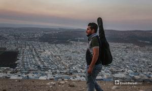 مازن الشيخ يحمل جيتاره على تله بلدة عقربات المطلة على المخيمات والقرى -08 أيلول 2020 (عنب بلدي/ يوسف غريبي)