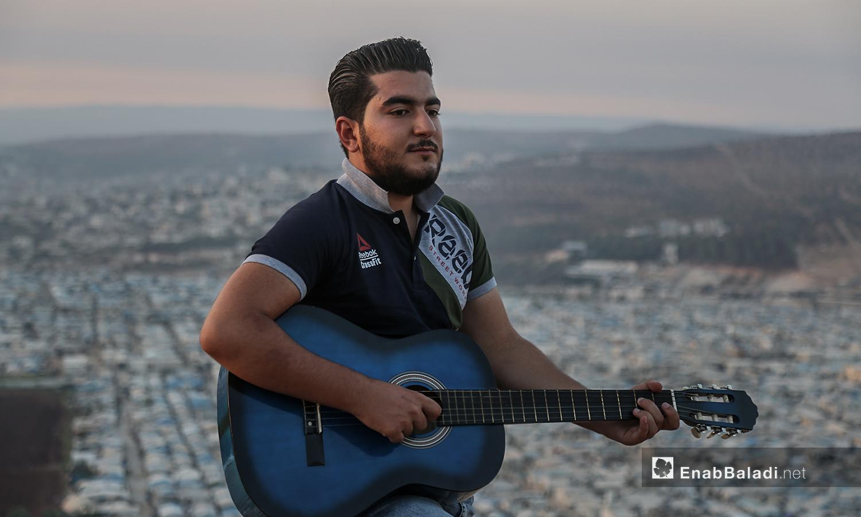 مازن الشيخ يعزف على تله بلدة عقربات المطلة على المخيمات والقرى  -08 أيلول 2020 (عنب بلدي/ يوسف غريبي)