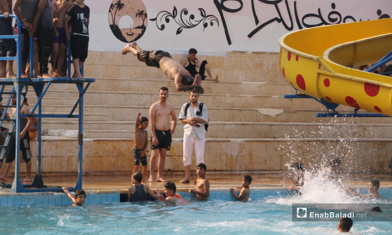 """أشخاص يسبحون في مسبح """"إدلب البلدي"""" وسط موجة ارتفاع للحرارة - أيلول 2020 (عنب بلدي/ أنس الخولي)"""