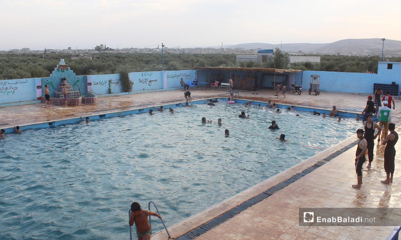 """أطفال يسبحون في مسبح """"الإرادة"""" في كللي بريف إدلب الشمالي - أيلول 2020 (عنب بلدي/ إياد عبد الجواد)"""