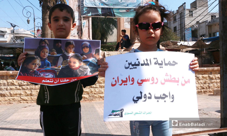 أطفال يحملون لافتات تندد بانتهاكات حلفاء النظام السوري في وقفة احتجاجية بساعة الساحة في إدلب - 25 أيلول 2020 (عنب بلدي/ أنس الخولي)