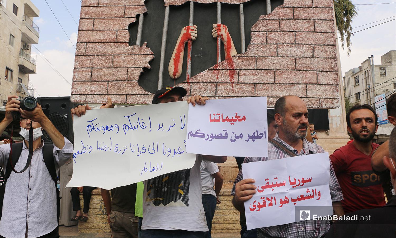 متظاهرون يقفون أمام صورة تعبيرية عن معاناة الشعب السوري ويحملون لافتات تندد بالتعامل الدولي مع الأزمة الإنسانية - 11 أيلول 2020 (عنب بلدي/ أنس الخولي)