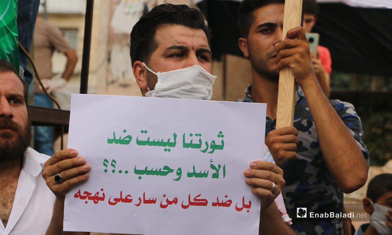 """متظاهر يرفع لافتة في مظاهرة إدلب تقول """"ثورتنا ليست ضد الأسد وحسب بل ضد كل من سار على نهجه"""" - 11 أيلول 2020 (عنب بلدي/ أنس الخولي)"""
