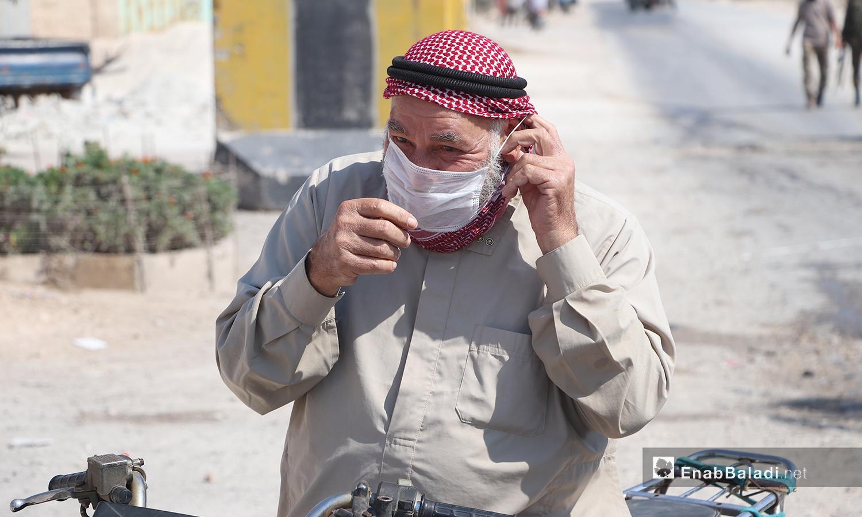"""رجل يرتدي كمامة قدمها له متطوعو الدفاع المدني ضمن حملة للتوعية بفيروس """"كورونا"""" في مدينة الباب - 24 أيلول 2020 (عنب بلدي/ عاصم الملحم)"""
