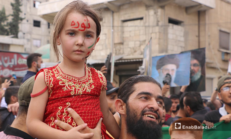 أب يرفع ابنته التي تحمل اسم الثورة على جبنها في أثناء مظاهرة في إدلب - 11 أيلول 2020 (عنب بلدي/ أنس الخولي)
