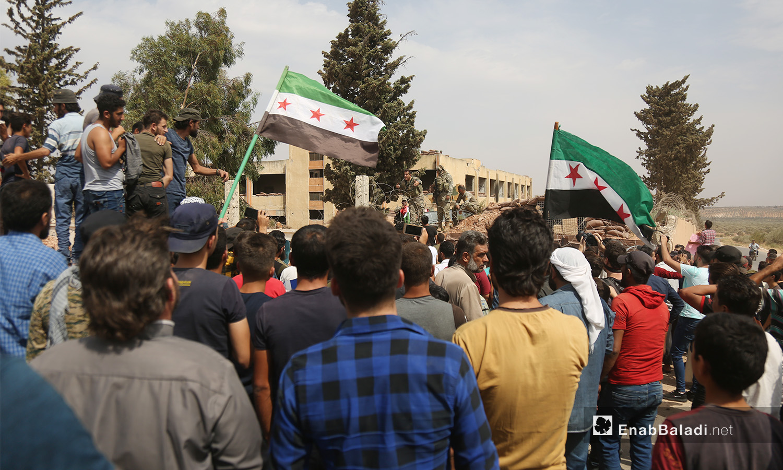 يرفع المتظاهرون أعلام الثورة أمام النقطة العسكرية التركية في بلدة المسطومة جنوبي إدلب - 11 أيلول 2020 (عنب بلدي)