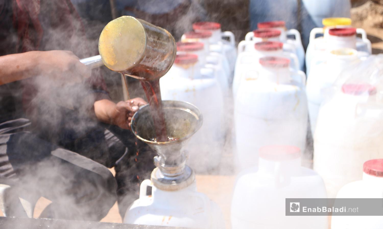 يسكب الدبس في العلب بعد إنهاء عملية التبريد - 17 أيلول 2020 (عنب بلدي/ عبد السلام مجعان)