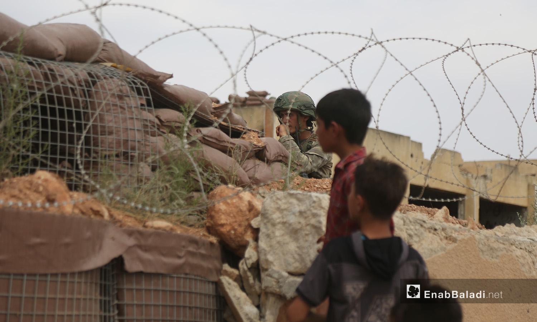 ينظر طفلان إلى النقطة العسكرية التركية التي تحيطها الأسلاك الشائكة في بلدة المسطومة جنوبي إدلب - 11 أيلول 2020 (عنب بلدي)