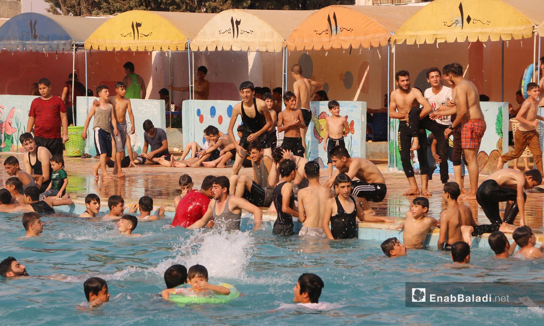 """ازدحام في مسبح """"إدلب البلدي"""" دون إجراءات اتخاذ إجراءات الوقاية من فيروس """"كورونا"""" - أيلول 2020 (عنب بلدي/ أنس الخولي)"""