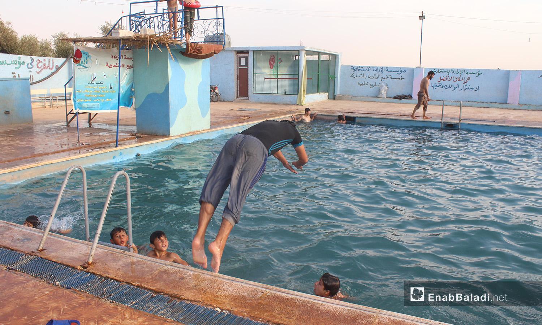 """شاب يقفز إلى الماء في مسبح """"الإرادة"""" في كللي بريف إدلب الشمالي - أيلول 2020 (عنب بلدي/ إياد عبد الجواد)"""