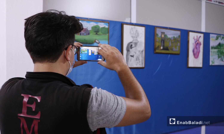 زائر يصور اللوحات المعروضة في معرض الرسم في مدينة الباب - 22 أيلول 2020 (عنب بلدي/ عاصم الملحم)