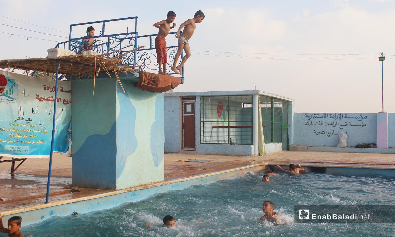 """أطفال يستعدون للقفز بالماء في مسبح """"الإرادة"""" في كللي بريف إدلب الشمالي -أيلول 2020 (عنب بلدي/ إياد عبد الجواد)"""