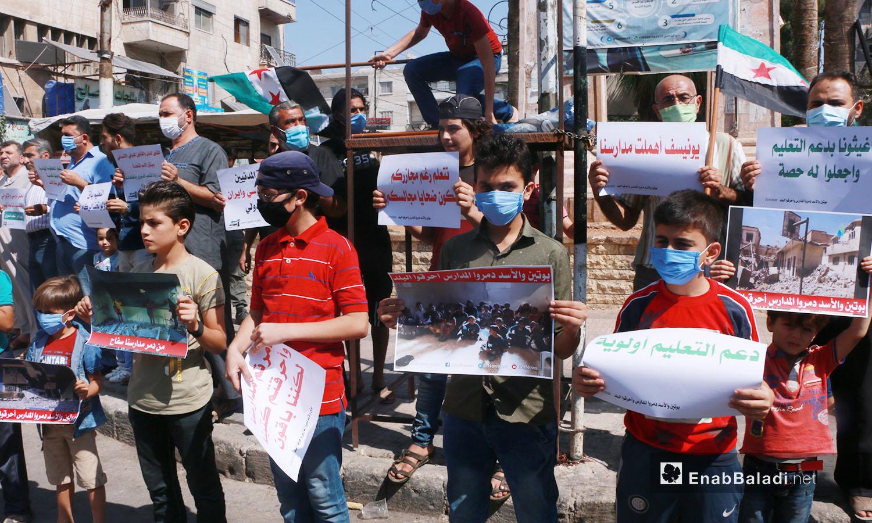 وقف الناشطون في ساحة الساعة في إدلب حاملين اللافتات والصور للاحتجاج على استهداف المدارس من قبل النظام السوري وحلفائه - 25 أيلول 2020 (عنب بلدي/ أنس الخولي)
