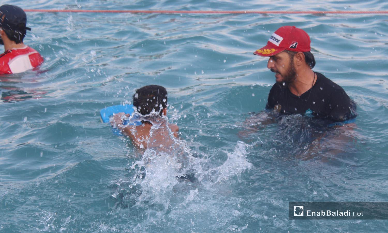 مدرب يساعد طفلًا على تعلم السباحة - أيلول 2020 (عنب بلدي/ إياد عبد الجواد)
