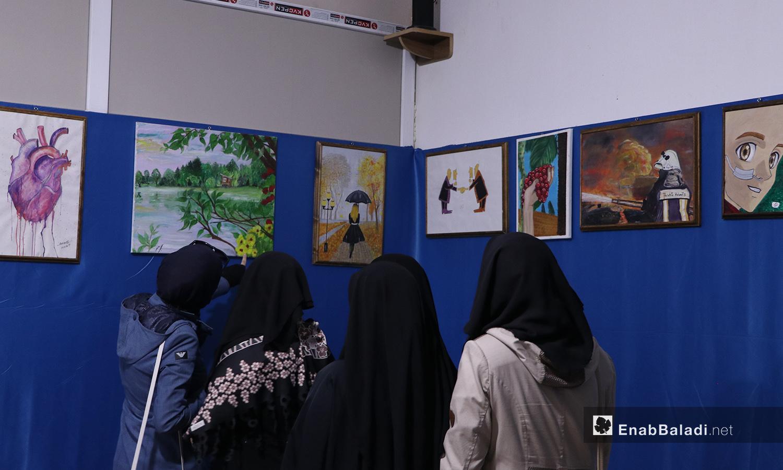 مجموعة من زائرات معرض الرسم في مدينة الباب يشاهدن اللوحات المعروضة - 22 أيلول 2020 (عنب بلدي/ عاصم الملحم)