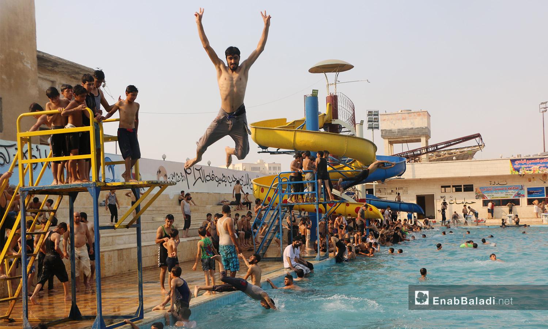 """شخص يقفز إلى الماء في مسبح """"إدلب البلدي"""" - أيلول 2020 (عنب بلدي/ أنس الخولي)"""