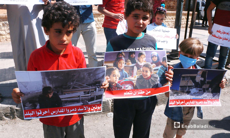 """أطفال يحملون صورًا ولا فتات كتب عليها """"من حقنا أن نتعلم"""" - 25 أيلول 2020 (عنب بلدي/ أنس الخولي)"""