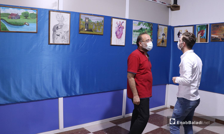 زائران لمعرض الرسم في مدينة الباب يشاهدان اللوحات المعروضة - 22 أيلول 2020 (عنب بلدي/ عاصم الملحم)