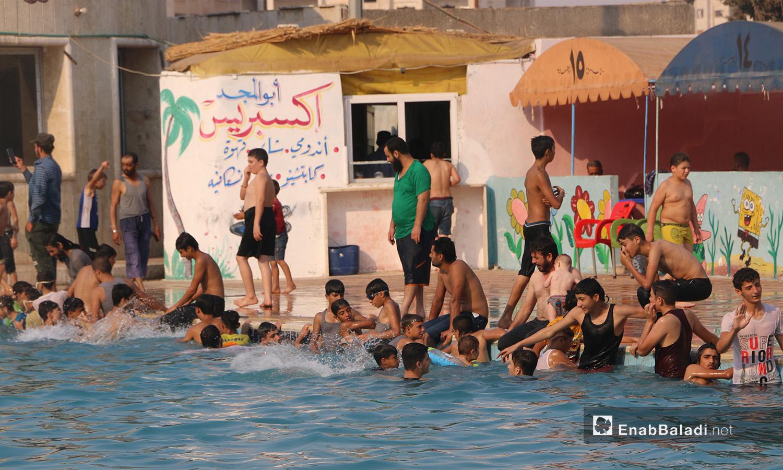 """مجموعة من الشباب والأطفال في مسبح """"إدلب البلدي"""" - أيلول 2020 (عنب بلدي/ أنس الخولي)"""