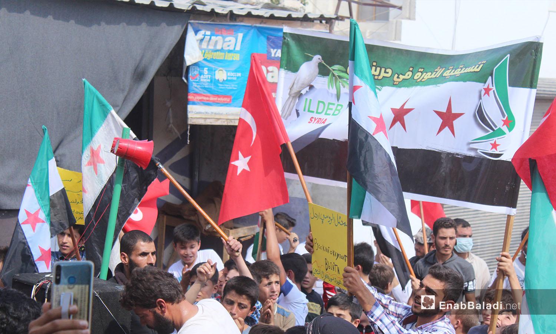 علم الثورة السورية والعلم التركي مرفوعان في مظاهرة بقرية حربنوش في ريف إدلب الشمالي - 25 أيلول 2020 (عنب بلدي/ إياد عبد الجواد)