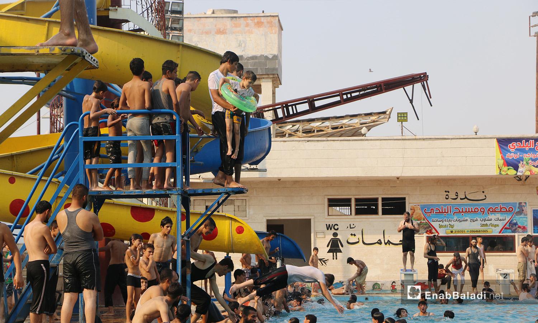 """أطفال وشباب يتزاحمون للقفز في مسبح """"إدلب البلدي"""" - أيلول 2020 (عنب بلدي/ أنس الخولي)"""