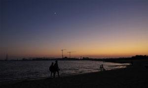 أشخاص يمشون على شاطئ جزيرة قبرص - 22 آب 2020 (AP)