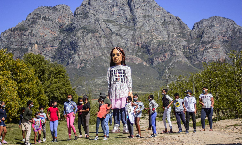 الدمية أمل التي تمثل الطفلة السورية اللاجئة التي تنتقل عبر رحلة لجوئها من سوريا إلى أوروبا (Bevan Roos/PA)