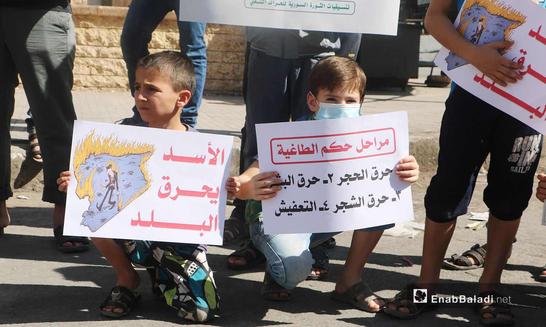 طفلان يحملان لافتات تشير إلى انتهاكات النظام السوري بحق المدنيين ضمن وقفة احتجاجية في إدلب - 9 تشرين الأول 2020 (عنب بلدي/ أنس الخولي)