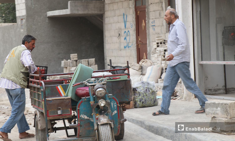 رجل يمشي على الرصيف متجهًا إلى عربته في مدينة الرقة - أيلول 2020 (عنب بلدي/ عبد العزيز الصالح)