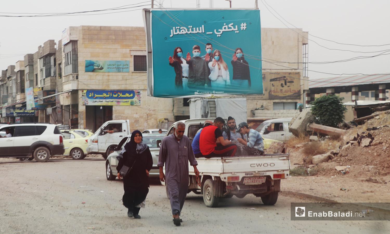 """أشخاص يمشون في الشارع في مدينة الرقة وتظهر لافتة تحث الناس على الاهتمام بالوقاية من فيروس """"كورونا"""" - أيلول 2020 (عنب بلدي/ عبد العزيز الصالح)"""