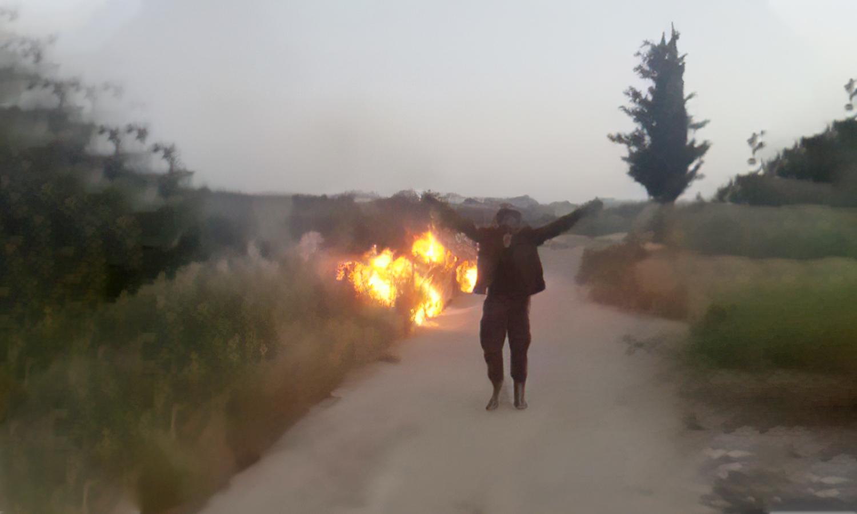 شخص بلباس عسكري يضرم النار في أرض زراعية (من تسجيل مصور متداول)