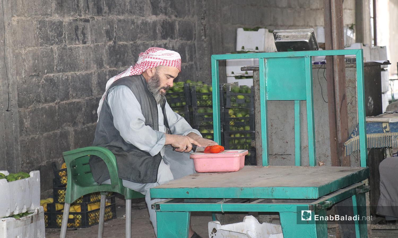 رجل يقطع الخضار في سوق الهال بمدينة الرقة - أيلول 2020 (عنب بلدي/ عبد العزيز الصالح)