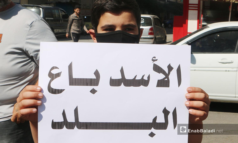 """طفل يحمل لافتة كتب عليها """"الأسد باع البلد"""" ضمن وقفة احتجاجية في إدلب - 9 تشرين الأول 2020 (عنب بلدي/ أنس الخولي)"""