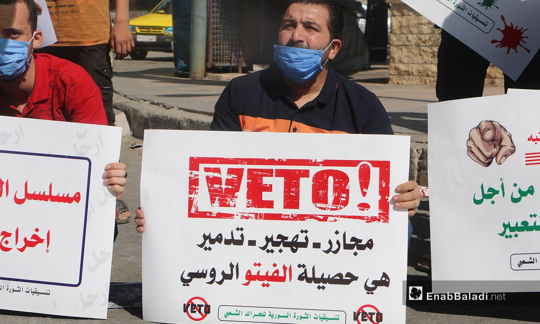 """ناشط يرفع لافتة تندد بالفيتو الروسي ضمن وقفة احتجاجية بعنوان """"المدنيون ضحايا إرهاب الأسد وداعميه"""" في مدينة إدلب - 9 تشرين الأول 2020 (عنب بلدي/ أنس الخولي)"""