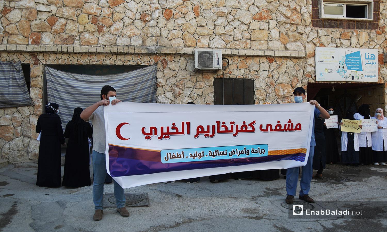 """شباب يحملهون لافتة """"مشفى كفر تخاريم الخيري ويقفن بجانب الكادر الطبي النسائي ويدعمهن -11 تشرين الأول 2020 (عنب بلدي /يوسف غريبي)"""