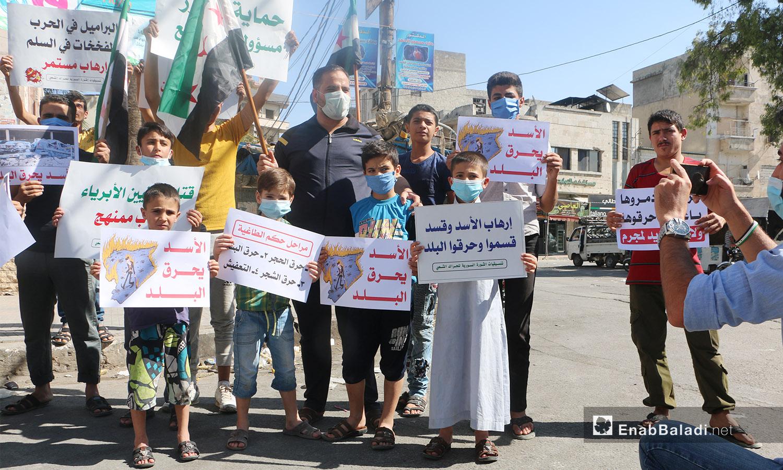 شارك الناشطون في الوقفة الاحتجاجية بمدينة إدلب رافعين لافتات تدين الانتهاكات بحق المدنيين في سوريا - 9 تشرين الأول 2020 (عنب بلدي/ أنس الخولي)