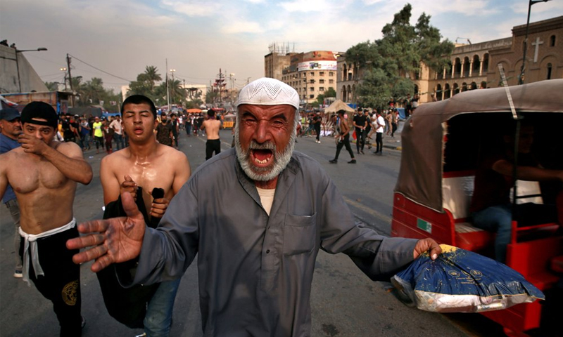 متظاهرون يعانون من آثار الغاز المسيل للدموع الذي أطلقته قوات الأمن العراقية لمنعهم من قطع جسر الجمهورية نحو المنطقة الخضراء في الذكرى الأولى لثورة تشرين - 25 تشرين الأول 2020 (AP)