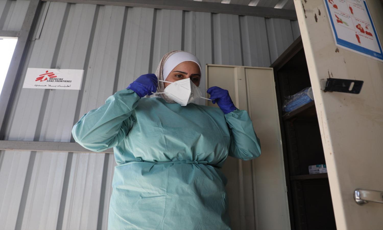 براءة مازن، ممرضة في منظمة أطباء بلا حدود في مركز علاج كوفيد-19 في مخيم الزعتري للاجئين، ترتدي ثوبا وقائيا قبل التعامل مع مرضى مصابين بالفيروس. 21 من تشرين الأول 2020 (محمد سنباني/ منظمة أطباء بلا حدود)