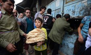 طفل سوري بعد حصوله على حصته من الخبز - المصدر (AFP)