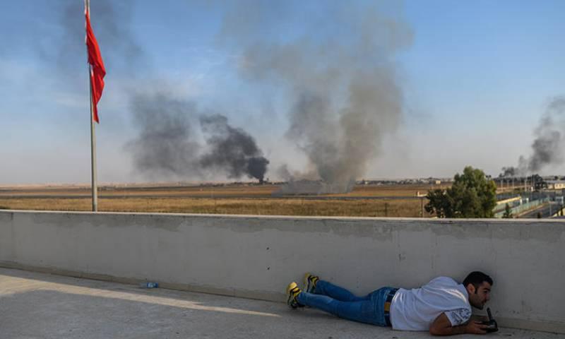 صحفي يختبئ في بلدة أكجاكال بالقرب من الحدود التركية- السورية في الوقت الذين سقطت فيها قذائف هاون قريبًا من المكان- 10 من تشرين الأول 2019 (فرانس برس/ بولينت كيليش)