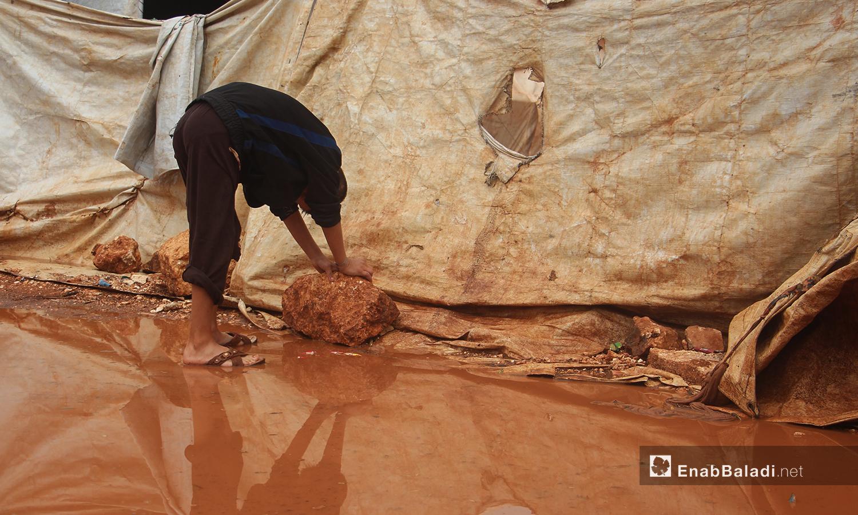 طفل يثبت الخيام بالحجارة بعد هطول الأمطار في مخيم الرمضون على أطراف قرية كفر عروق شمالي إدلب - 2 تشرين الثاني 2020 (عنب بلدي/إياد عبد الجواد)