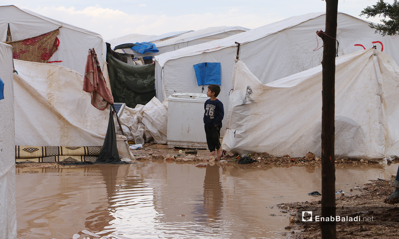 """طفل يقف أمام بركة من الماء متجمعة أمام خيمته في مخيم """"الفلاح"""" بريف حلب الشمالي  - 4 تشرين الثاني 2020 (عنب بلدي/ عبد السلام مجعان)"""