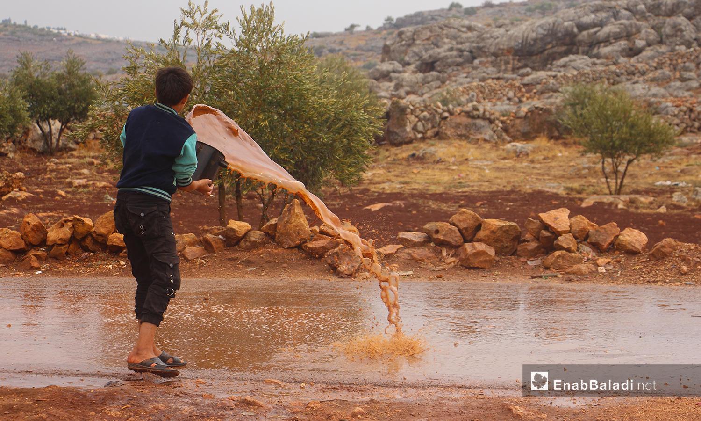 طفل يرمي المياه بعيدًا عن الخيم بعد هطول الأمطار في مخيم الرمضون على أطراف قرية كفر عروق شمالي إدلب - 2 تشرين الثاني 2020 (عنب بلدي/إياد عبد الجواد)