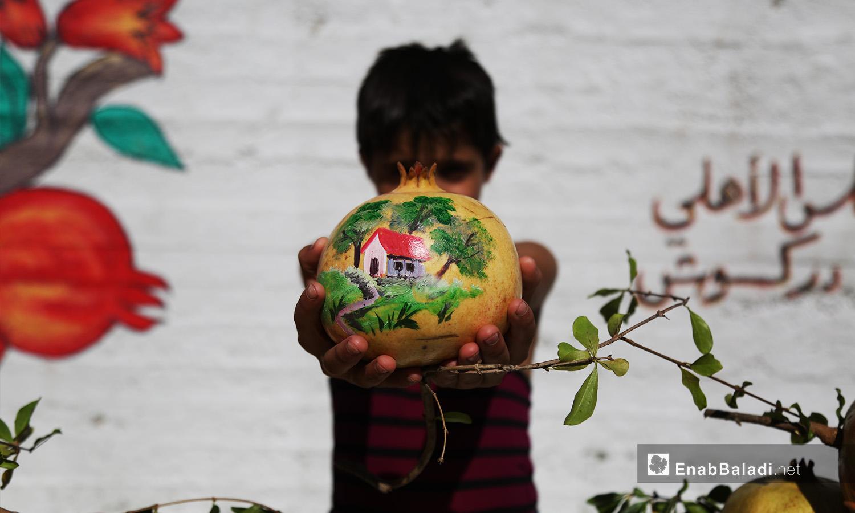 طفل يحمل رمانة رسم عليها لوحة مصغرة لبيت في الريف ضمن مهرجان الرمان في دركوش بريف إدلب الغربي - تشرين الأول 2020 (عنب بلدي/ يوسف غريبي)