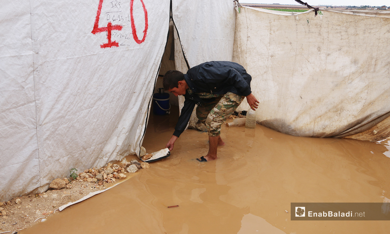 """طفل يحاول إبعاد الماء عن خيمته في مخيم """"الفلاح"""" بريف حلب الشمالي  - 4 تشرين الثاني 2020 (عنب بلدي/ عبد السلام مجعان)"""