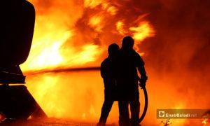 عنصرين من الدفاع المدني يخمدون الحريق الحاصل بعد انفجار مجهول على المتحلق الشمالي في مدينة الباب شمالي حلب - 2 تشرين الثاني 2020 (عنب بلدي/عاصم الملحم)