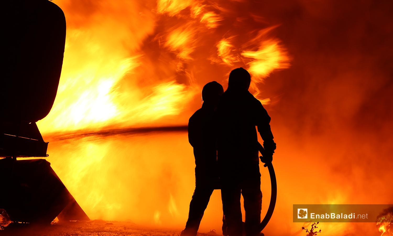 عنصران من الدفاع المدني يحاولان إخماد الحريق الحاصل بعد انفجار مجهول على المتحلق الشمالي في مدينة الباب شمالي حلب- 2 تشرين الثاني 2020 (عنب بلدي/عاصم الملحم)